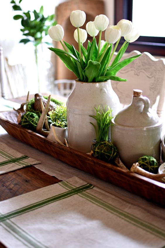 a stylish rustic spring centerpiece of a white tulip arrangement, moss balls and greenery, antlers and jugs