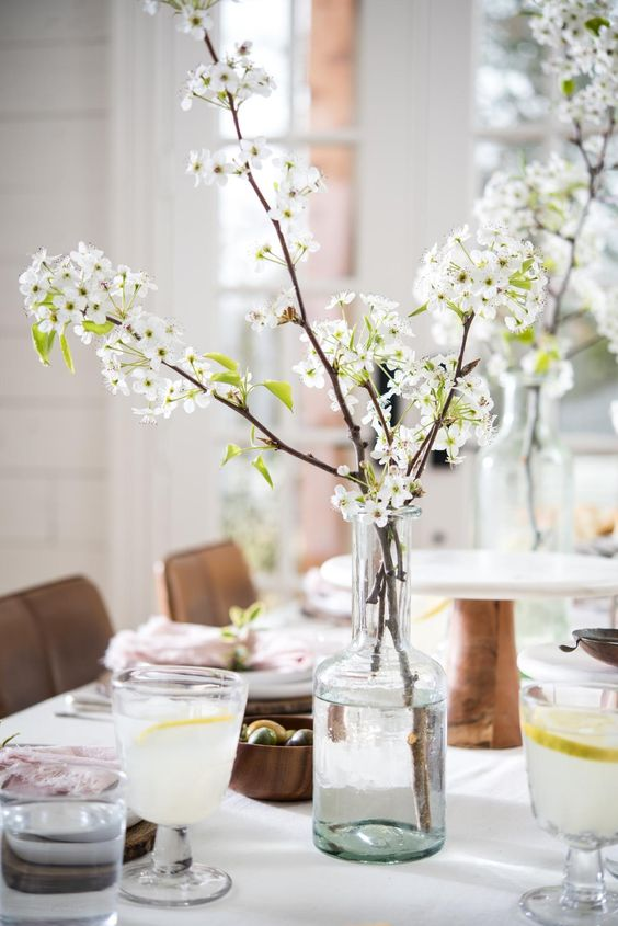a stylish spring tablescape with wooden bowls and placemats, simple glasses and a bottle with blooming branches