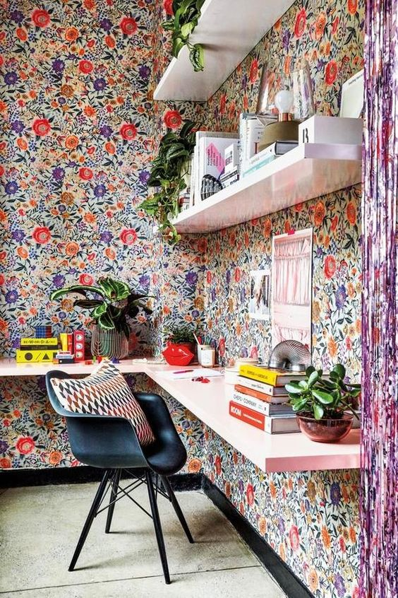 a super bold modern home office done with colorful floral wallpaper, open shelves and a floating pink desk