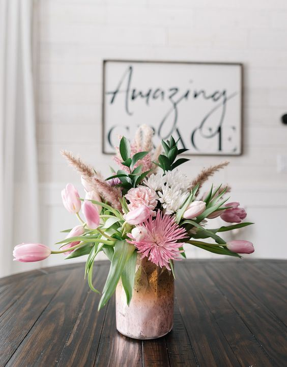 a tender pink floral arrangement with pink spray painted grasses in a copper and pink vase is a lovely centerpiece to rock