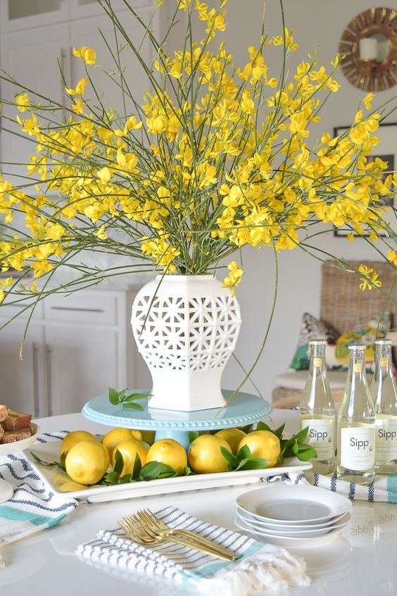 a tray with lemons, a vintage vase and yellow blooming branches compose a lovely and fun spring centerpiece