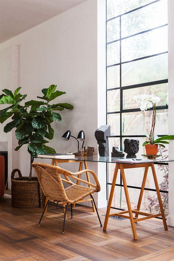 a trestle desk with a glass desktop, a rattan chair, potted plants and blooms and some rocks is a lovely idea for a boho home office