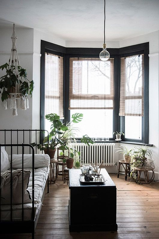 a vintage boho bedroom with a bay window that fills the space with light and gives it to potted plants creating a small orangery