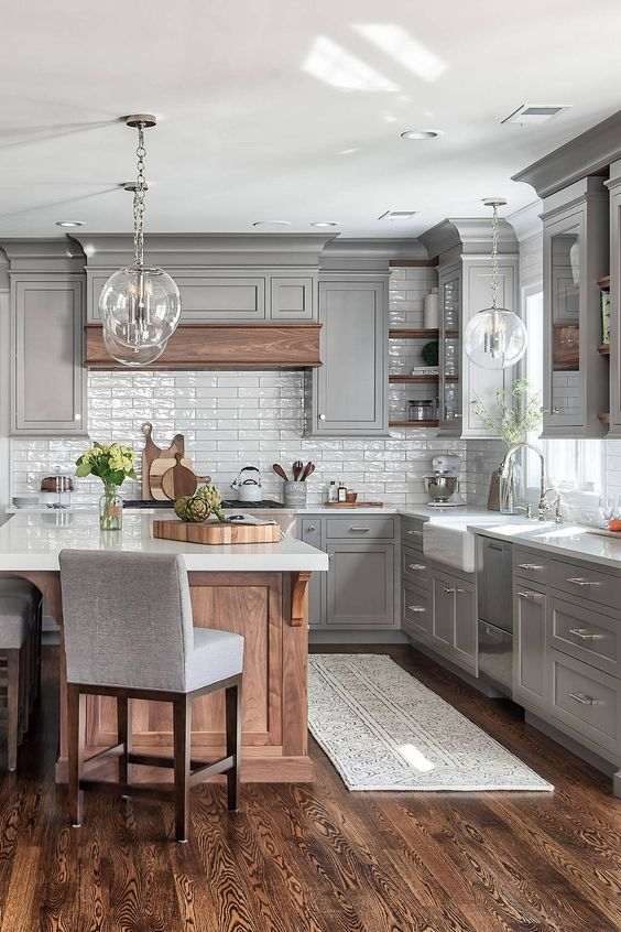 a vintage grey kitchen with a stained wooden island, a wooden hood, a white tile backsplash and glass sphere lamps