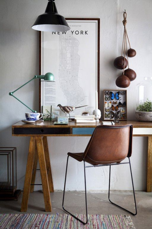a vintage home office with a wooden trestle desk and color block drawers, a leather chair, some lamps and artworks