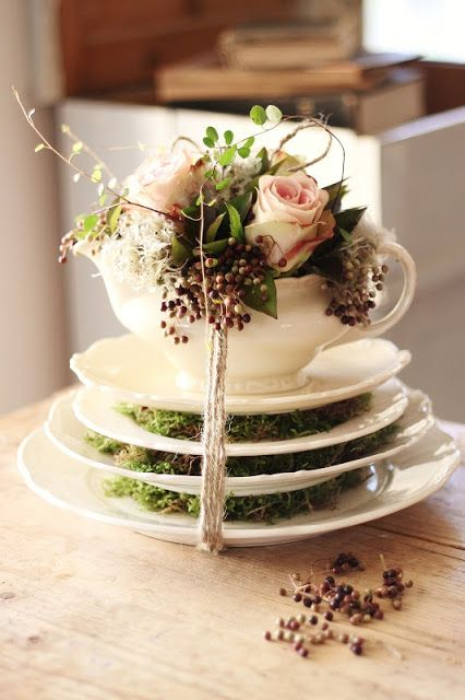 a vintage spring centerpiece of a stack of saucepans with moss, a saucepan with roses and greenery is amazing and refined