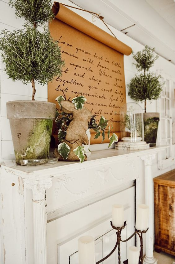a vintage spring mantel with greenery topiaries, leaves, a bunny figurine, greenery in a cloche and a quote on kraft paper