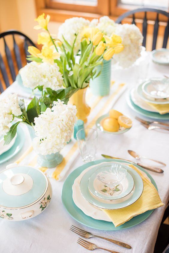 a vintage spring tablescape with turquoise and yellow vases, matching plates and napkins, lemons and blooms plus a striped runner
