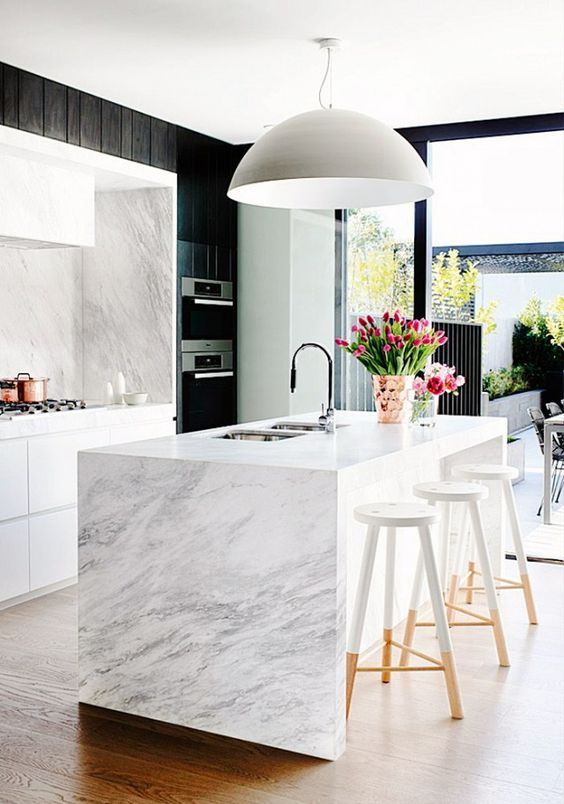 a vivacious contemporary kitchen with white cabinetry and a marble kitchen island, black paneling, a large pendant lamp and color block stools