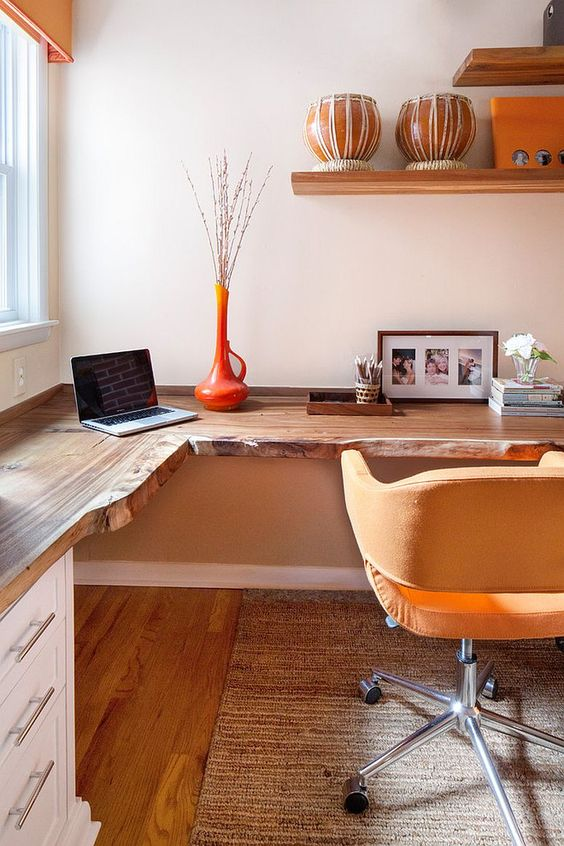 a warm-colored modern home office with a corner desk with a living edge, a yellow chair, some open shelves and bright accessories