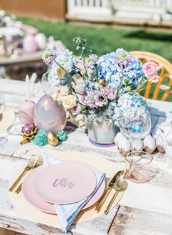 a watercolor Easter tablescape with pink plates, blue napkins, lilac, blush and blue florals and pastel-colored eggs