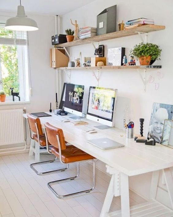 a welcoming and airy home office with open shelves, a white shared trestle desk, leather chairs and pendant lamps plus books