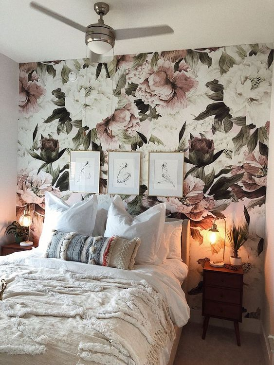 a welcoming and romantic bedroom with a chic pink floral wall, a neutral bed and table lamps that imitate blooms