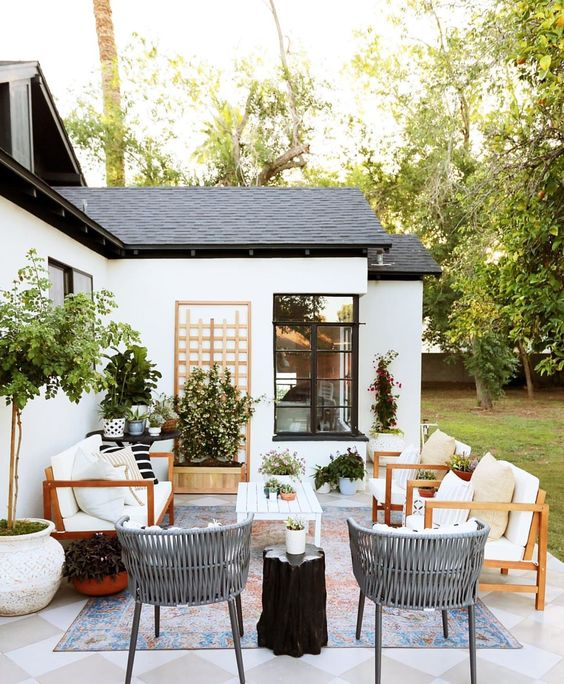 a welcoming modern terrace with potted greenery and trees, white furniture, a tree stump table is very welcoming