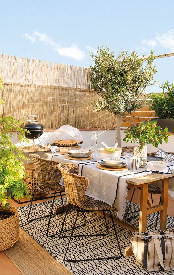 a welcoming spring terrace with a dining space, a wooden table and rattan chairs, potted greenery and trees