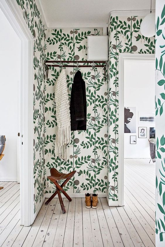 a whimsical wallpapered hallway with a stool and a rack looks very fresh and welcoming thanks to the green shades on the wallpaper