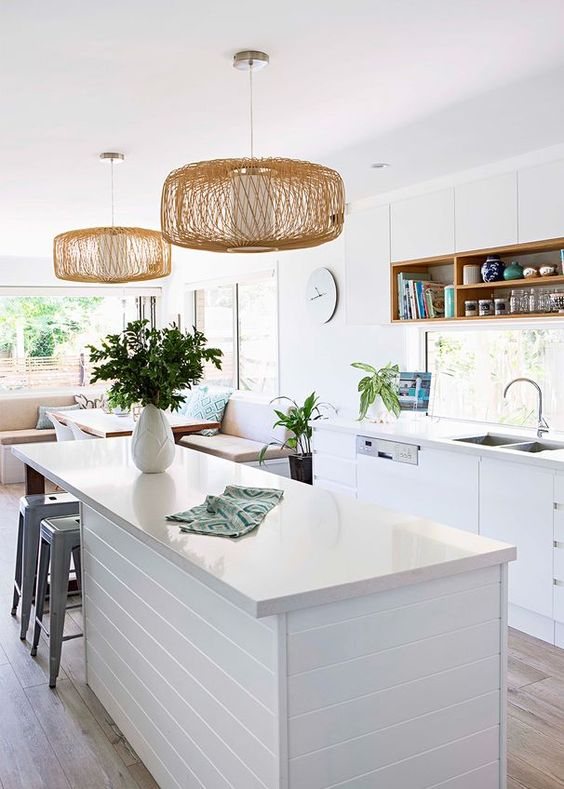 a white boho coastal kitchen with chic cabinets, a window as a backsplash, wicker pendant lamps and greenery