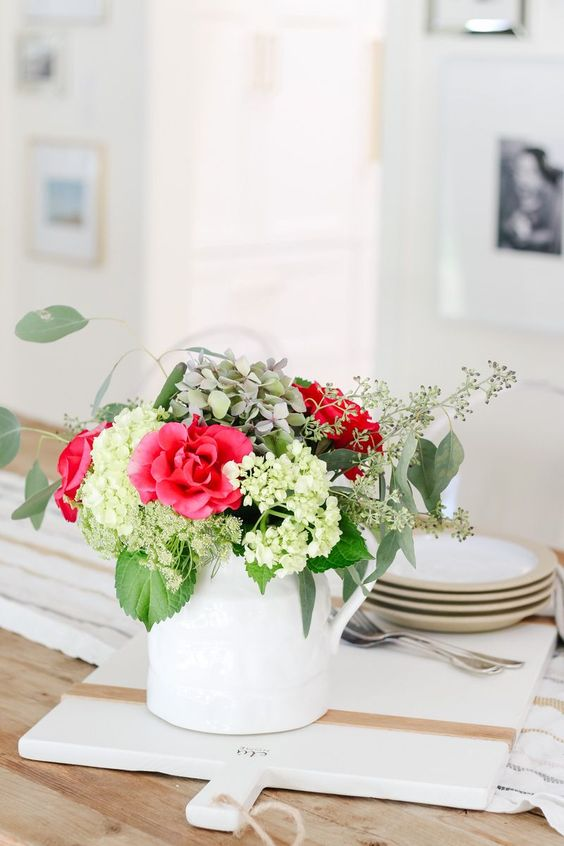 a white jug with bold red blooms, green flowers and greenery is a bright floral arrangement for spring or summer