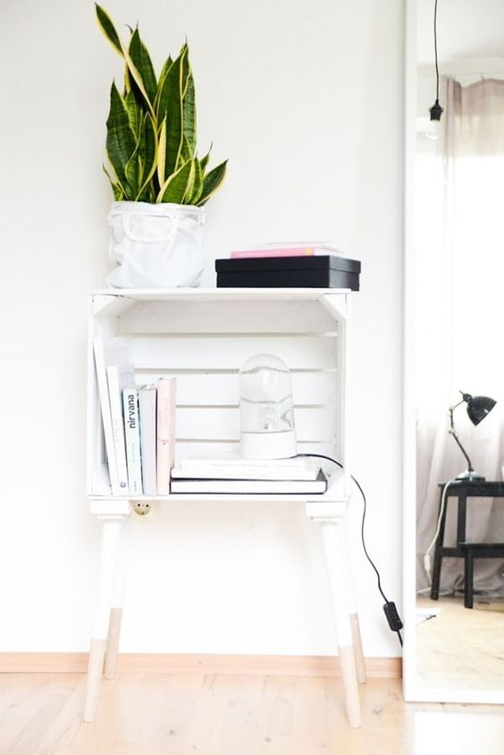 a white nightstand of a crate on legs used for books, potted plants and other stuff is a creative idea for any modern space