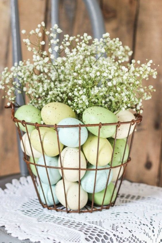 a wire basket with pastel eggs and gypsophilia on top is a lovely spring centerpiece or decoration to rock