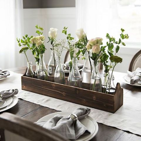 a wooden toolbox with bottles, white blooms and greeneyr for a rustic and relaxed spring centerpiece