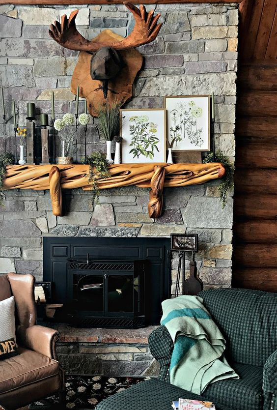 a woodland spring mantel or rough wood, with floral prints, potted greenery and blooms, candles and antlers cut out of wood