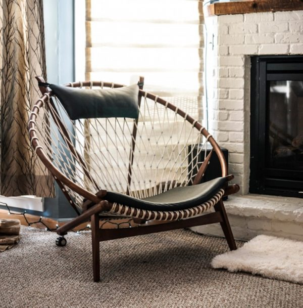 a woven papasan chair with leather cushions by the fireplace, layered rugs and lights for a welcoming nook