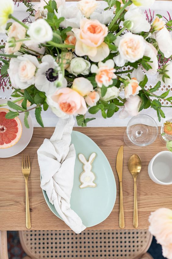 an Easter table setting with pastel blooms, a mint-colored egg-shaped plate, gold cutlery and bunny cookies