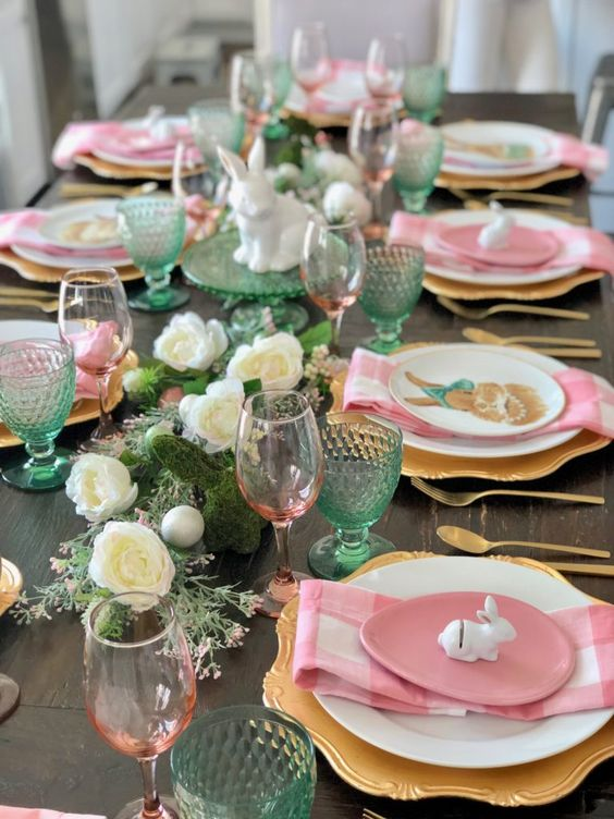 an Easter tablescape with white blooms and greenery, pink and green glasses, gold chargers and pink egg-shaped plates and pink plaid napkins