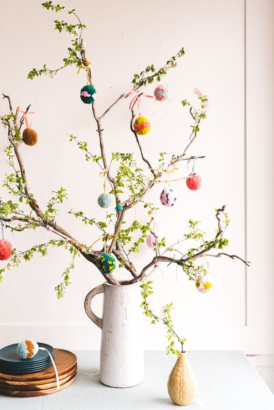 an Easter tree – greenery branches with colorful pompoms hanging is a cool and creative spring centerpiece idea