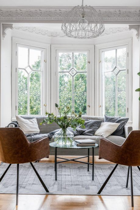 an airy and chic living room with stucco and a bay window that houses a grey sofa and leather chairs, a cool table and a chandelier