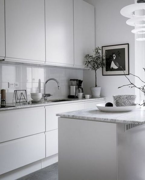an airy minimalist kitchen with white cabinets with no handles, white stone countertops and a grey glass backsplash is all chic