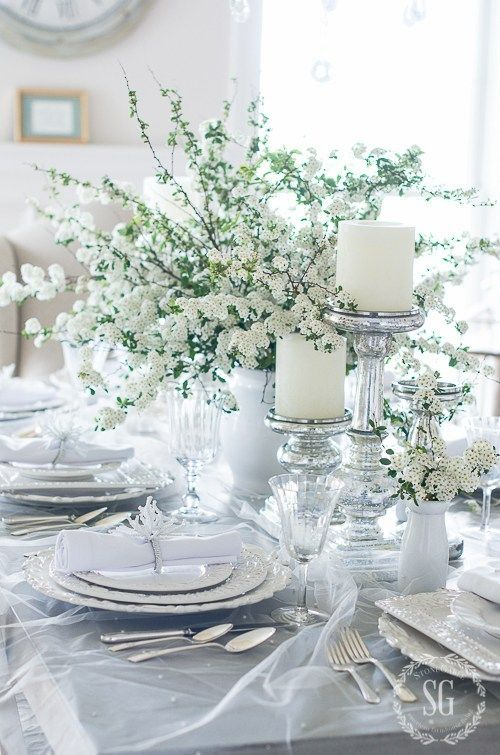 an airy spring table setting in white, with pillar candles, blooms, porcelain and a veil over the tablcloth for a light feel