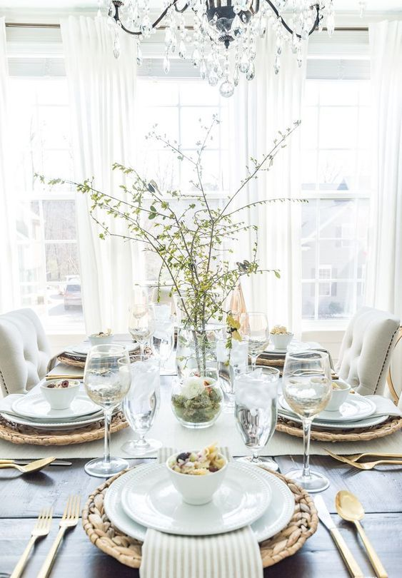 an airy spring tablescape with woven placemats, white porcelain and striped napkins, greenery branches and gold cutlery