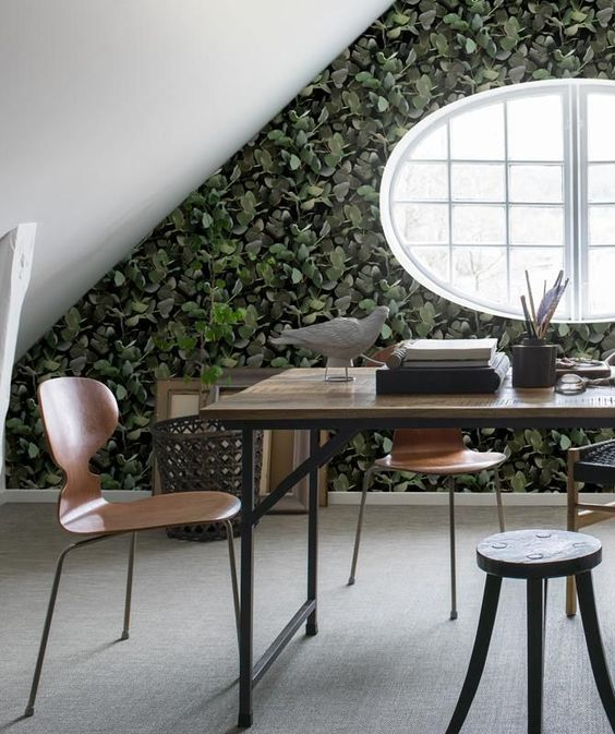 an attic workspace is made extremely eye-catchy with a eucalyptus print wallpaper wall that looks like real leaves