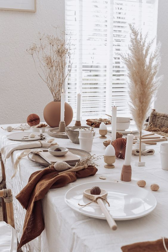 an earthy tone Easter table with white and grey porcelain, grasses in vases, candles, wooden spoons and terracotta napkins