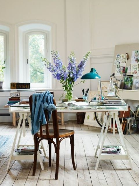 an eclectic home office with a white trestle desk with a glass desktop, a vintage chair and a blue lamp plus botanical posters around