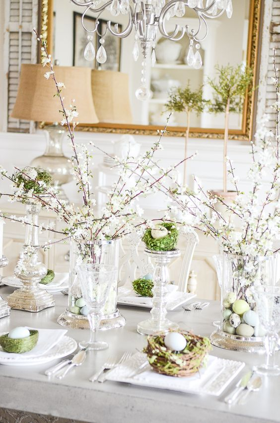 an elegant Easter brunch tablescape with blooming branches, nests with eggs, elegant candleholders with eggs