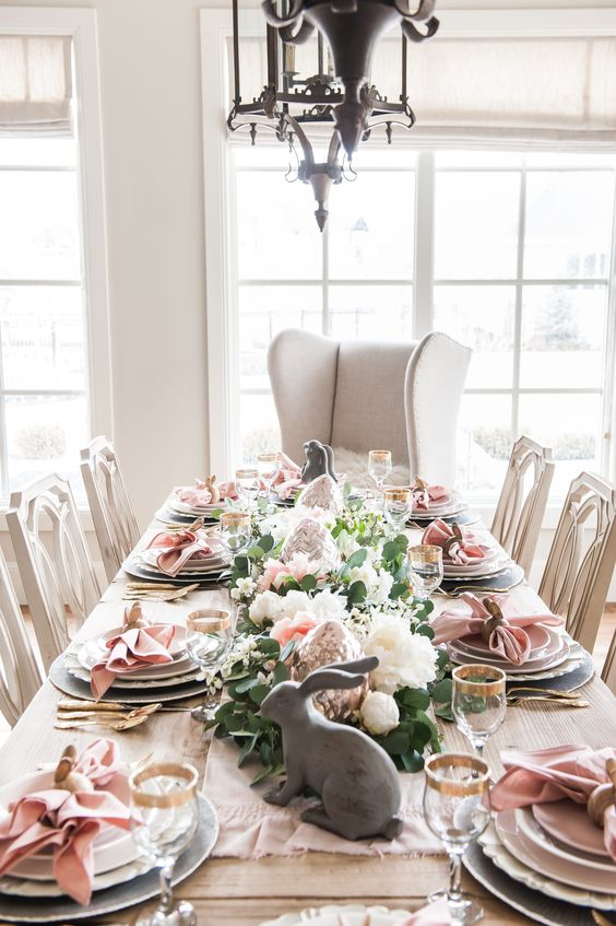 an elegant Easter tablescape with pink napkins, pink and white blooms and greenery, bunny figurines and gold rimmed glasses