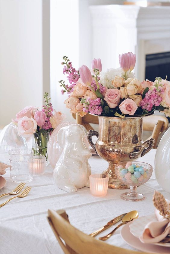 an elegant and chic Easter table setting with a lovely floral centerpiece, candles, porcelain bunnies, gold cutlery and pastel candies