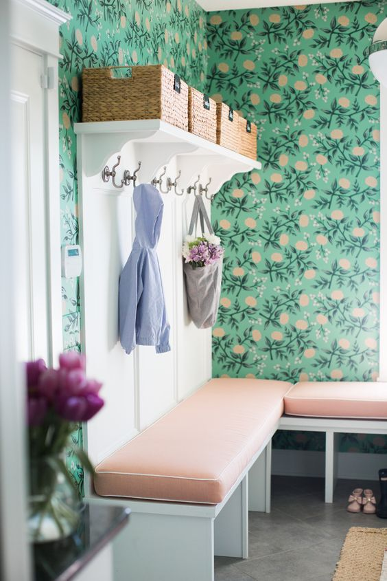 an elegant farmhouse mudroom with bright floral wallpaper, a built-in seat in white and blush pink and baskets