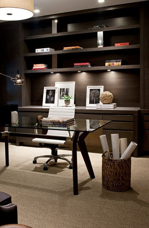 an elegant modern home office in dark shades, with a large built in storage unit, a glass and wood desk, a leather chair and some lights