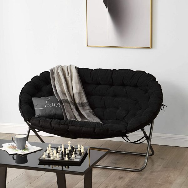 an elegant nook with a black folding papasan chair with a pillow and a blanket, chess on the table and a bold art
