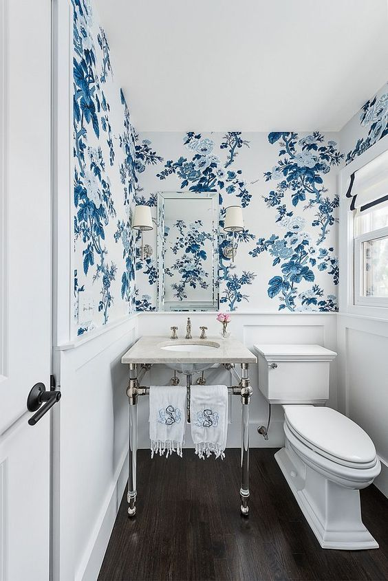 an elegant restroom done in creamy and neutrals and with pretty blue and white floral wallpaper is gorgeous and chic