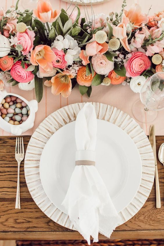 an elegant spring brunch tablescape with a pink runner, bold florals, pastel candies and simple cutlery