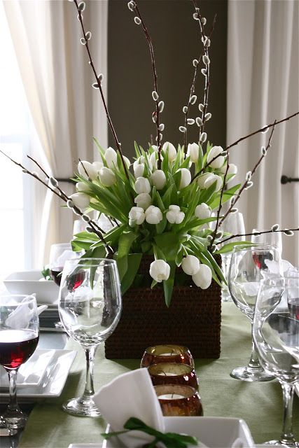 an elegant spring centerpiece of a black vase, white tulips and willow is a stylish idea that you can easily realize yourself
