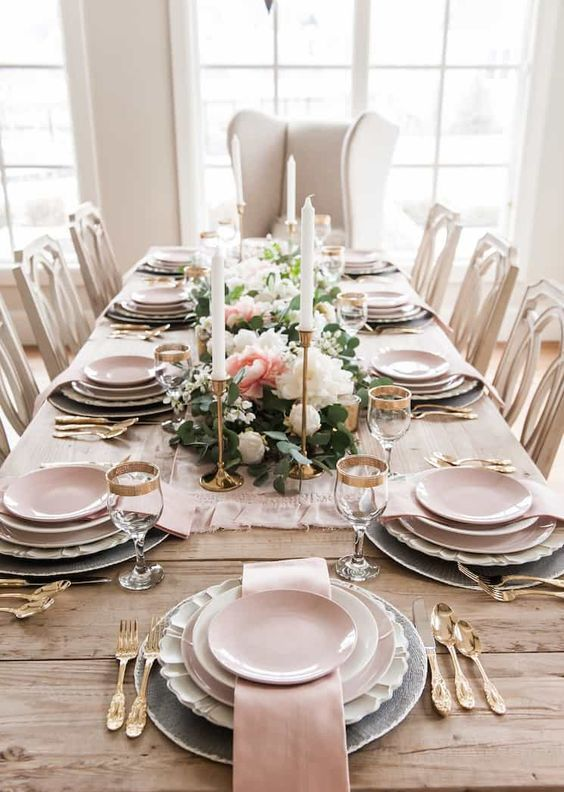 an elegant spring tablescape with white and pink blooms, candles, pink plates and napkins and refined gold cutlery