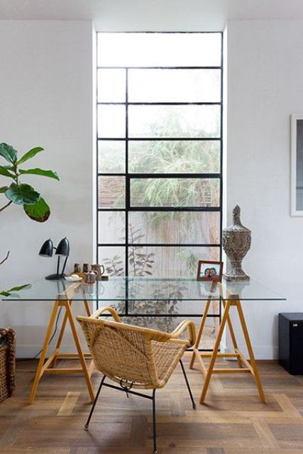 an elegant working space with a glass trestle desk, a rattan chair, a statement plant and some decor plus a view