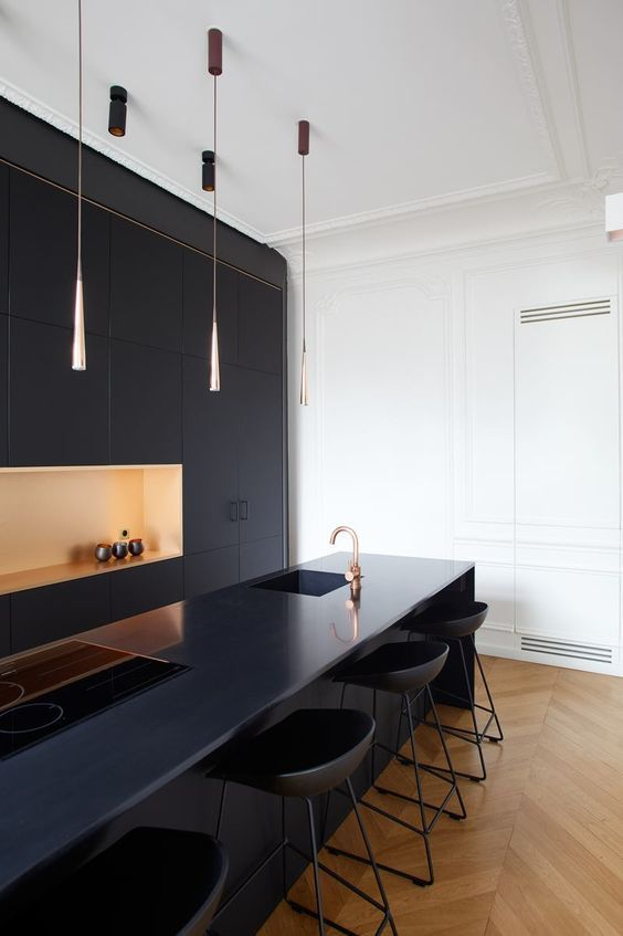 an ultra-minimalist navy kitchen wiht a yellow niche, catchy pendant lamps, a large island with built-in appliances and chic stools