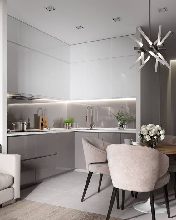an ultra-minimalist two-tone kitchen with sleek white and grey cabinets, a grey glass backsplash, built-in lights and grey chairs